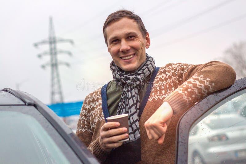 Um homem novo considerável está ao lado de um café de sorriso e bebendo do carro fotografia de stock royalty free