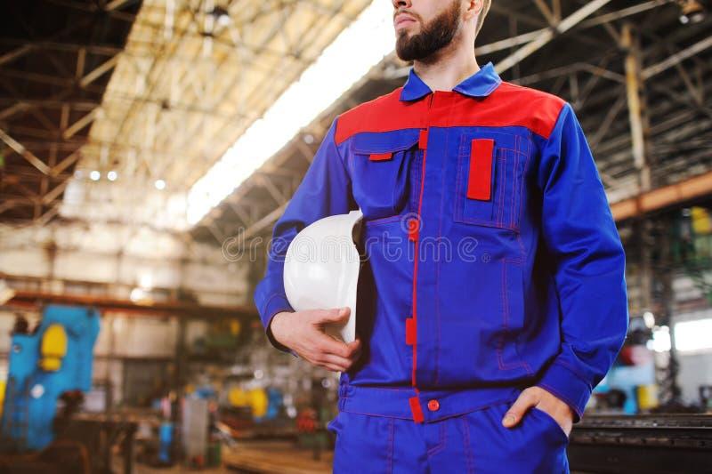 Um homem novo considerável - um trabalhador ou um coordenador com um capacete branco da construção em suas mãos contra o contexto imagem de stock royalty free