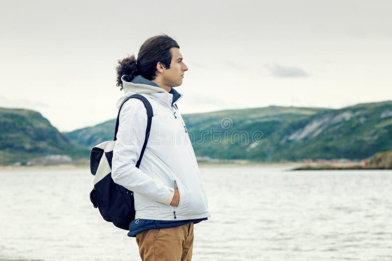 Um homem novo contra o contexto de montanhas ferozes e do mar imagens de stock