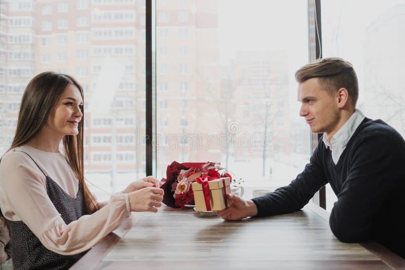 Um homem novo dá um presente com uma fita vermelha a uma menina, sua esposa, em um café pela janela fotos de stock royalty free