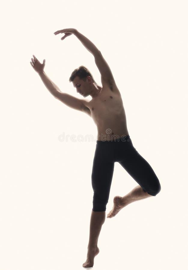 Um homem novo, dançarino de bailado, estando em um pé no ar, fundo amarelo imagem de stock royalty free