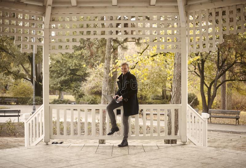 Um homem novo de sorriso, 20-29 anos velho, sentando-se na cerca fora no parque, ao usar seu port?til fotografia de stock royalty free