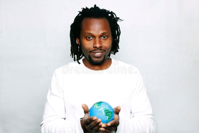 Um homem novo de sorriso guarda o globo do mundo em suas mãos imagens de stock royalty free