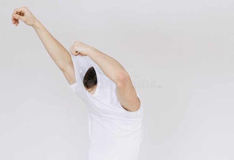 Um homem novo decola seu t-shirt Fundo cinzento isolado fotografia de stock