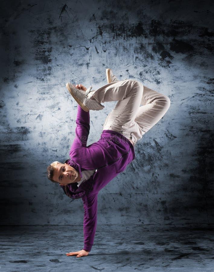 Um homem novo e desportivo que faz uma pose da dança moderna imagem de stock