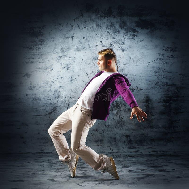 Um homem novo e desportivo que faz uma pose da dança moderna foto de stock