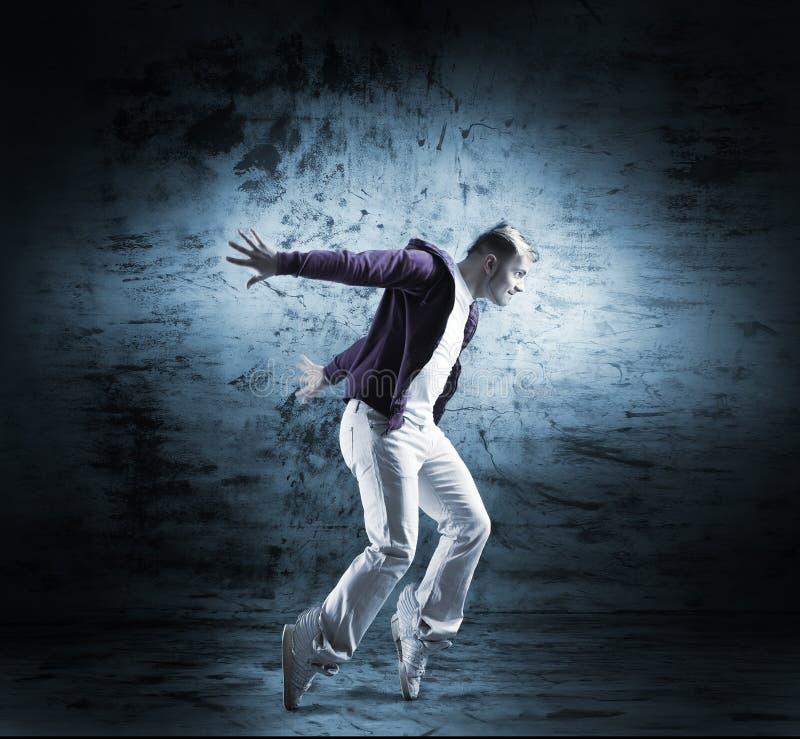 Um homem novo e desportivo que faz uma pose da dança moderna fotografia de stock