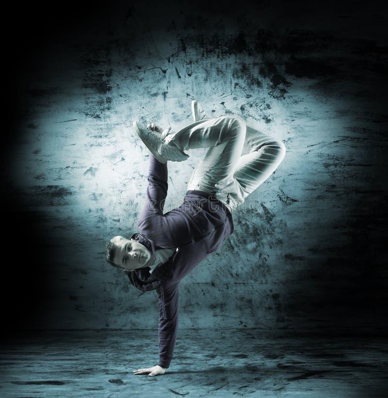 Um homem novo e desportivo que faz uma pose da dança moderna fotografia de stock royalty free