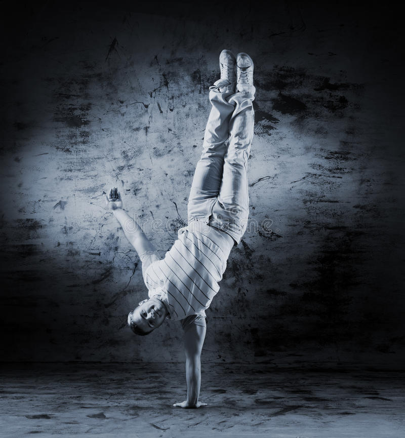 Um homem novo e desportivo que faz uma pose da dança moderna fotos de stock royalty free