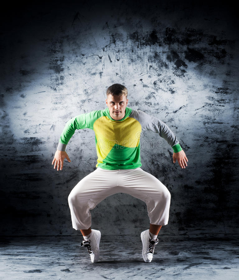 Um homem novo e desportivo que faz uma pose da dança moderna foto de stock royalty free