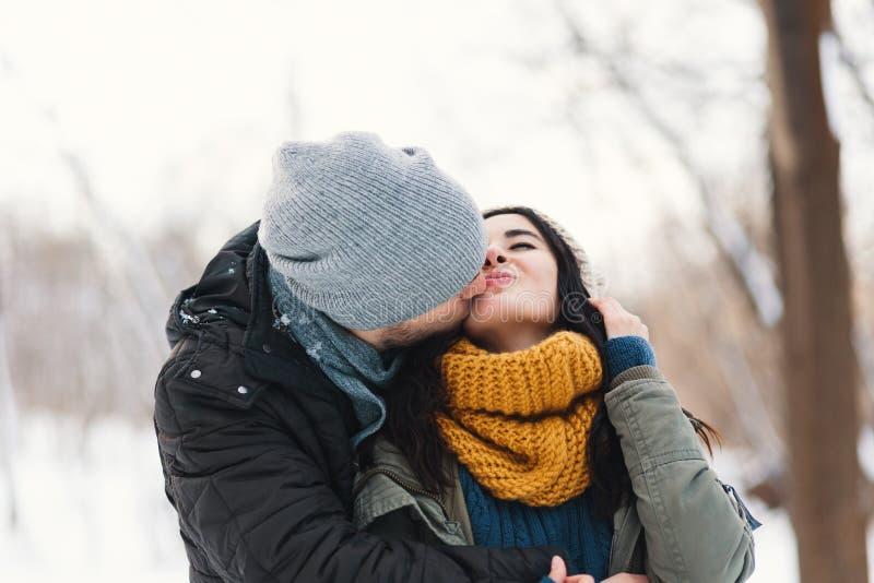 Um homem novo e uma mulher felizes que beijam no inverno que aprecia a vida e imagens de stock royalty free