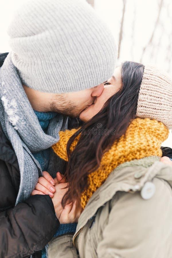 Um homem novo e uma mulher felizes que beijam no inverno que aprecia a vida e imagens de stock