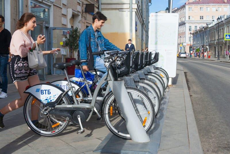 Um homem novo e uma mulher tomam uma bicicleta alugado no editorial da rua da cidade imagens de stock