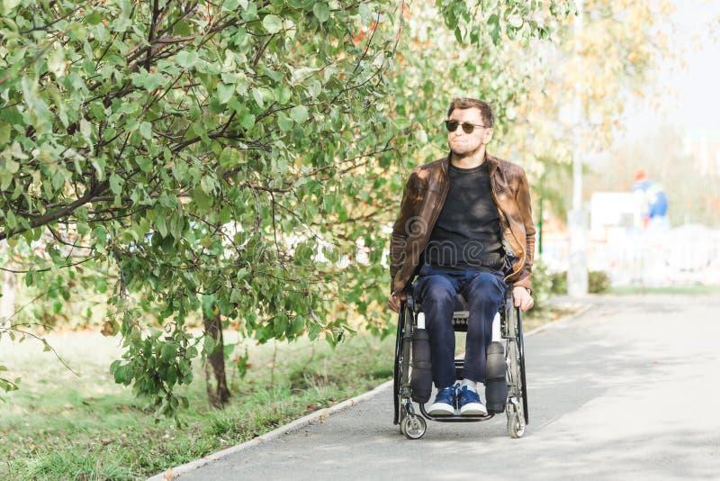 Um homem novo em passeios de uma cadeira de rodas ao longo da estrada do parque fotografia de stock