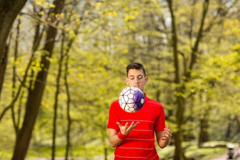 Um homem novo em um t-shirt vermelho joga com uma bola de futebol no parque verde Conceito do esporte imagens de stock royalty free