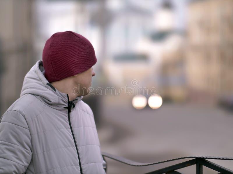 Um homem novo em um tampão vermelho está estando na rua que olha para trás fotografia de stock royalty free