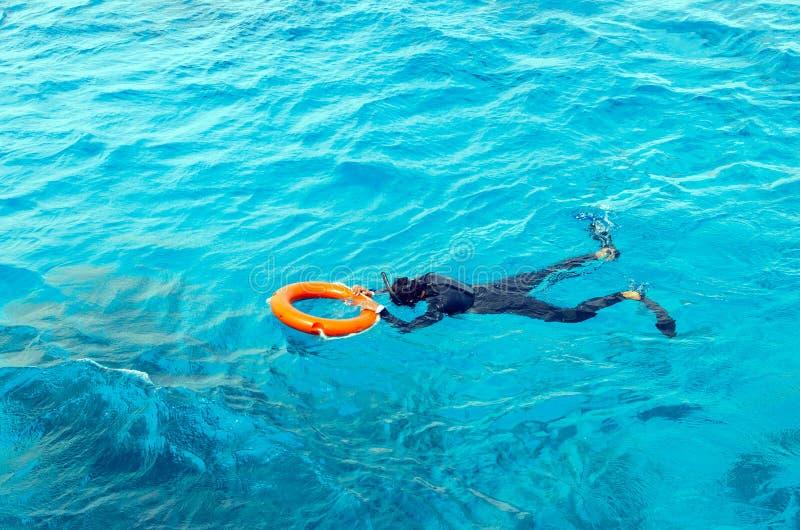 Um homem novo em um terno de mergulho e nadadas das aletas no mar que guarda o boia salva-vidas foto de stock