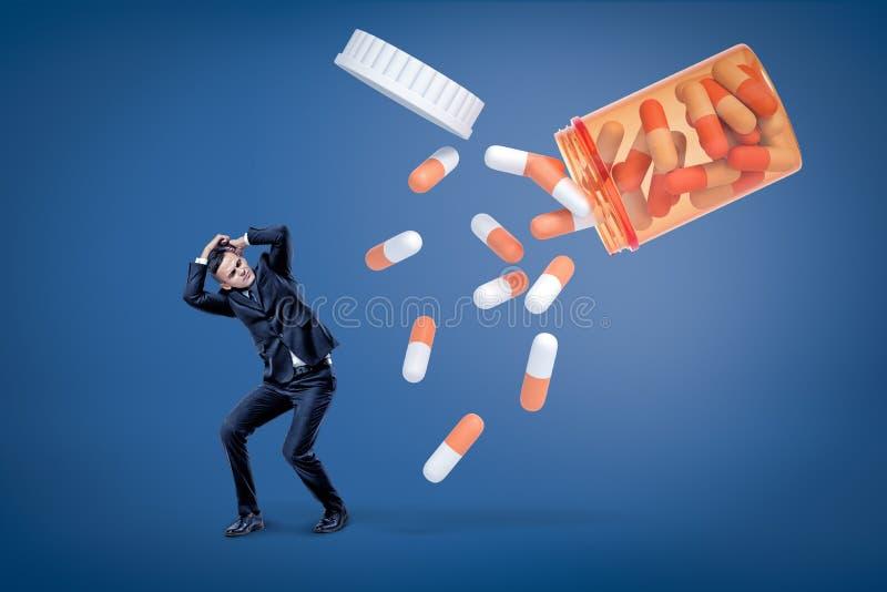 Um homem novo em um terno que tenta proteger-se de uma avalancha de comprimidos dois-coloridos enormes que saem de um frasco do c fotografia de stock
