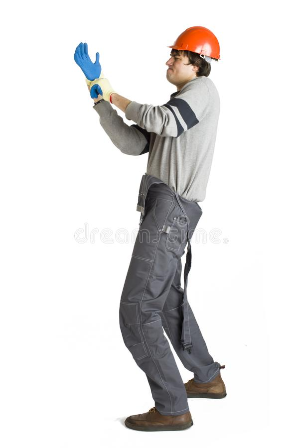 Um homem novo em trabalhar a roupa cinzenta e o capacete duro alaranjado que põem sobre uma luva no branco isolou o fundo fotos de stock