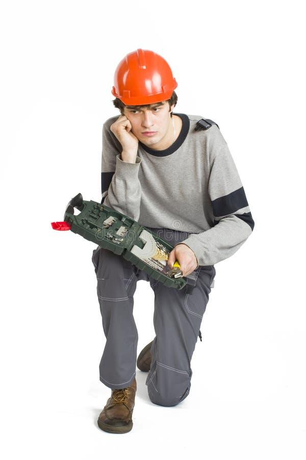 Um homem novo em trabalhar a roupa cinzenta e o capacete duro alaranjado que sentam-se com o conjunto de ferramentas no fundo bra imagens de stock royalty free