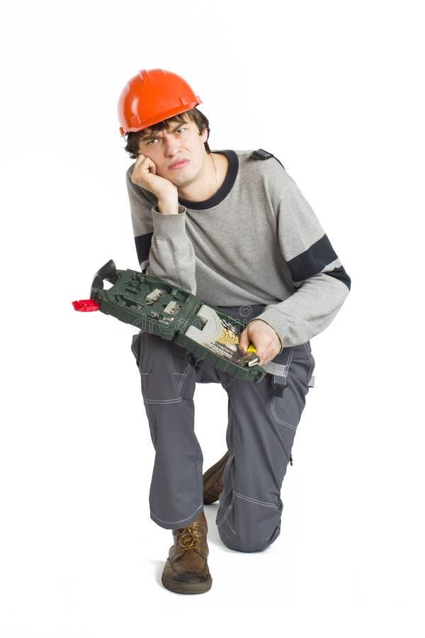 Um homem novo em trabalhar a roupa cinzenta e o capacete duro alaranjado que sentam-se com o conjunto de ferramentas no fundo bra fotografia de stock royalty free