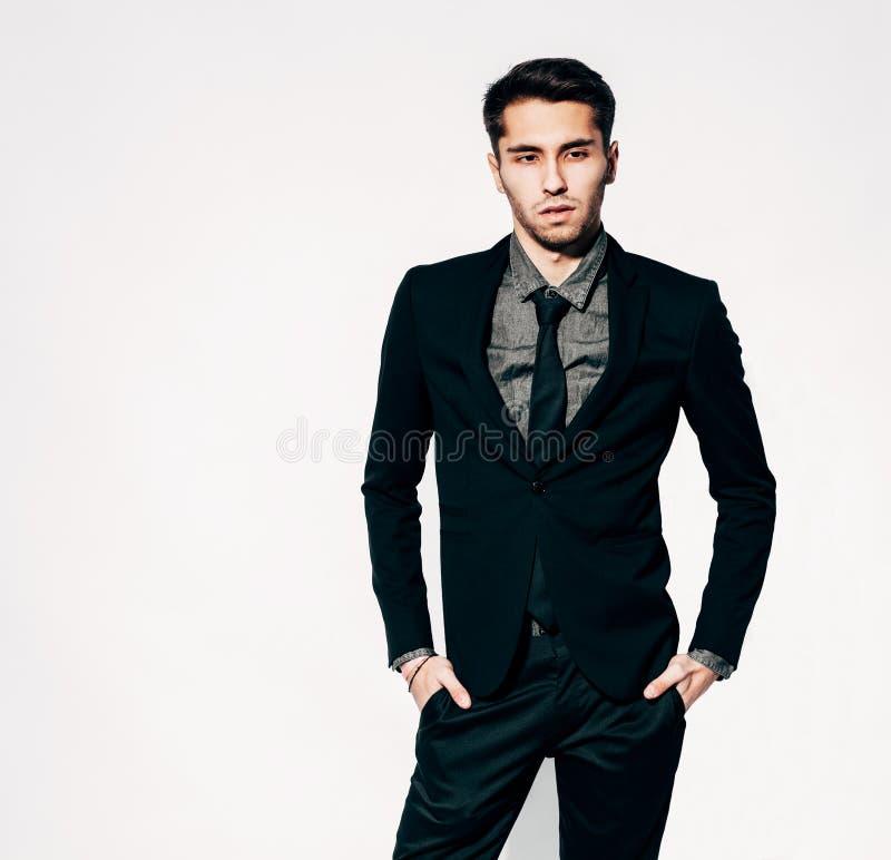 Um homem novo em um levantamento elegante do terno indoor Cor morna fotografia de stock
