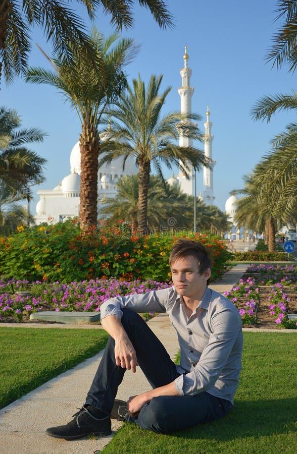 Um homem novo em um parque perto da mesquita imagem de stock royalty free