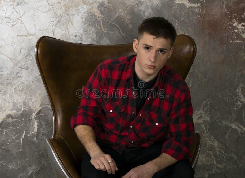 Um homem novo em uma camisa do moderno senta-se em uma cadeira bonita fotos de stock royalty free