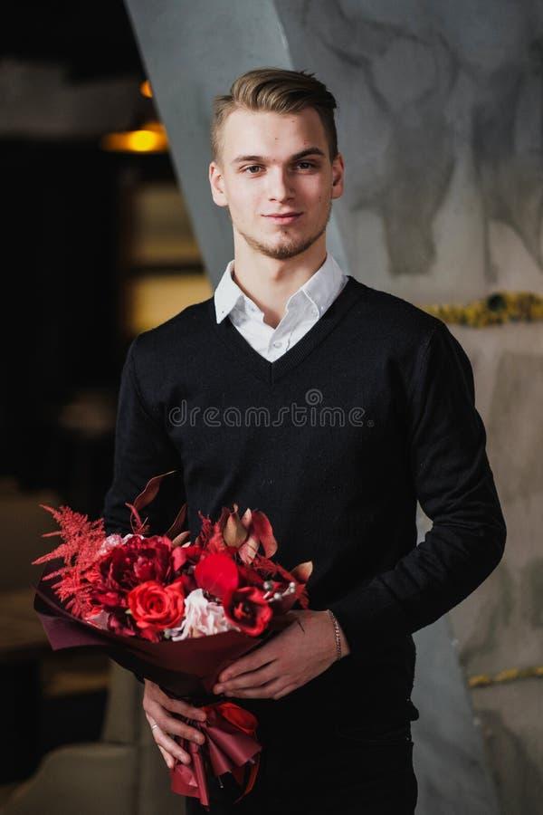 Um homem novo em uma camiseta preta e em uma camisa branca está guardando um ramalhete de flores vermelhas imagem de stock
