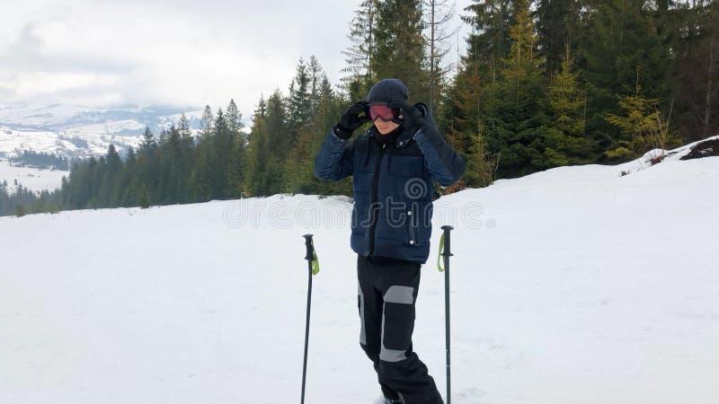 Um homem novo em vidros dos esportes está esquiando nas montanhas foto de stock