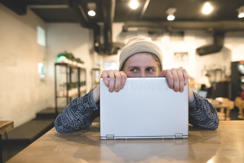 Um homem novo engraçado que esconde atrás de um portátil Os modernos alegres trabalham no computador em um café acolhedor Olhe af fotografia de stock royalty free