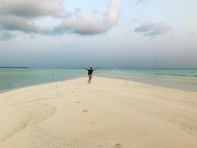 Um homem novo está correndo ao longo da praia imagem de stock