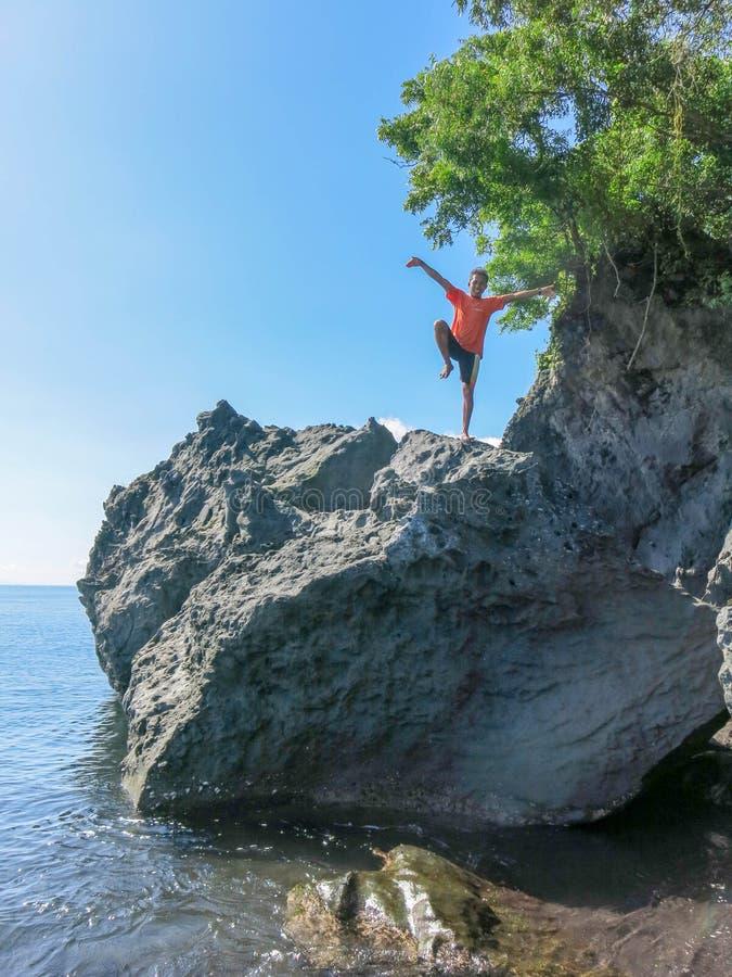 Um homem novo está em um pedregulho enorme nas formações de rocha da costa de origem vulcânica Os penhascos de formas abstratas fotografia de stock royalty free