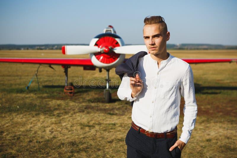 Um homem novo está perto de um avião Aviões pequenos para privado fotografia de stock royalty free