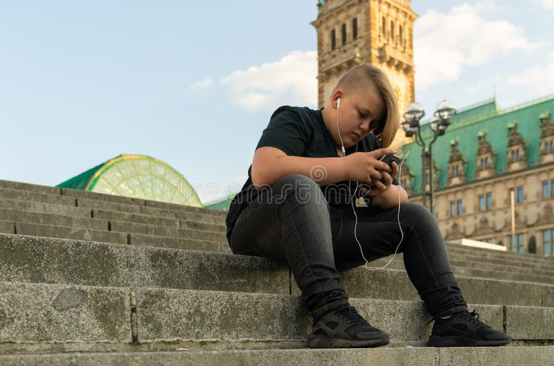 Um homem novo está sentando-se nas etapas e está olhando-se em seu telefone celular imagem de stock royalty free