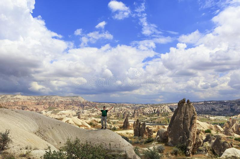 Um homem novo está sobre um monte e olha acima em um céu azul nebuloso em Cappadocia imagens de stock
