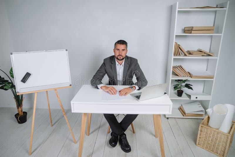 Um homem novo está trabalhando atrás de um portátil em seu escritório O professor prepara-se para a leitura fotos de stock royalty free
