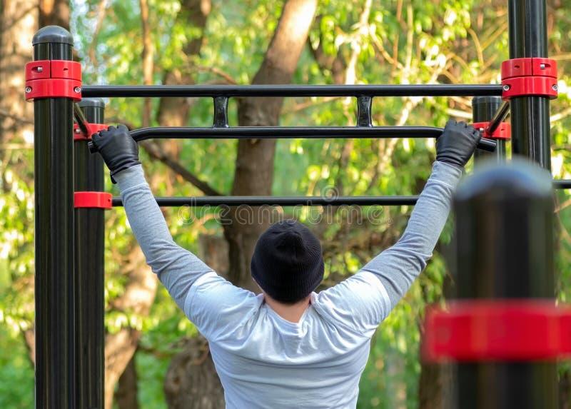 Um homem novo executa esportes exercita puxar na barra transversal do simulador O treinamento exterior desenvolve a for?a da part fotos de stock