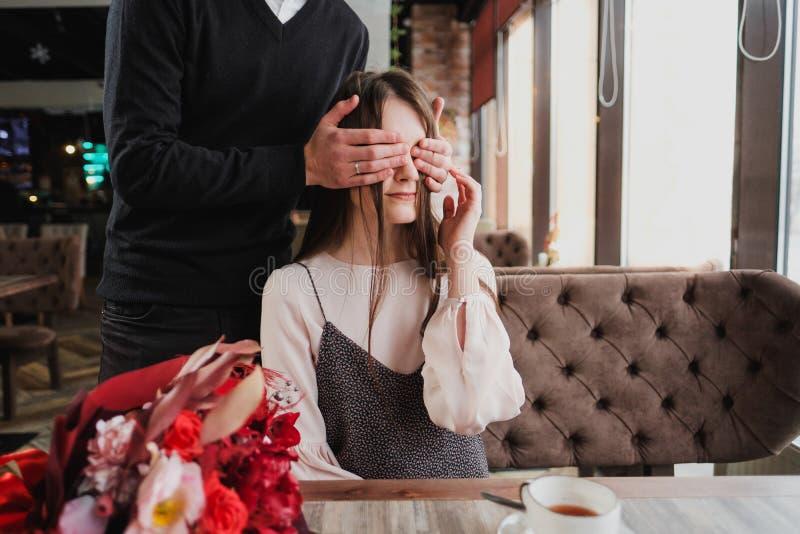 Um homem novo fecha seus olhos à menina, sua esposa, e dá um ramalhete de flores vermelhas em um café pela janela imagem de stock royalty free