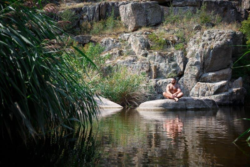 Um homem novo forte senta-se em uma rocha no meio da água no verão Natação do verão no rio entre rochas fotos de stock royalty free