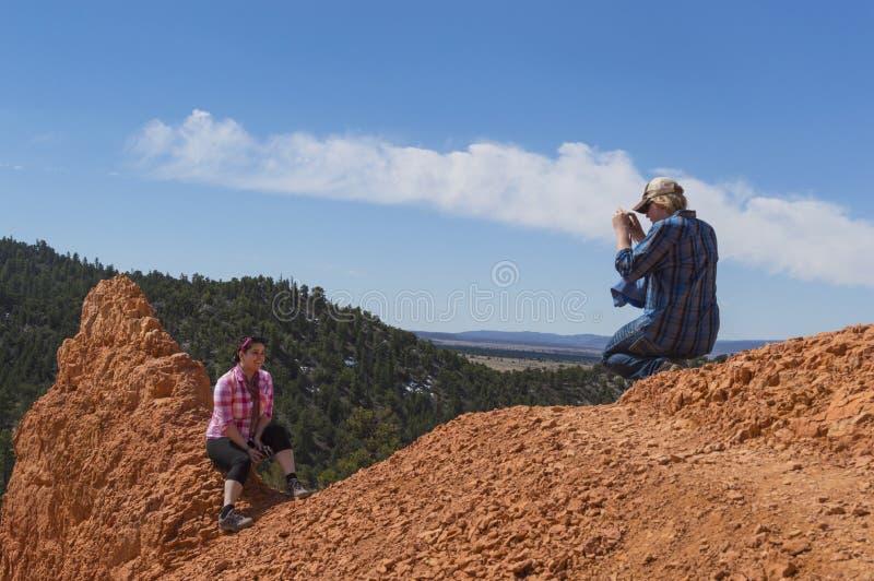 Um homem novo fotografa uma jovem mulher na garganta vermelha Utá imagens de stock