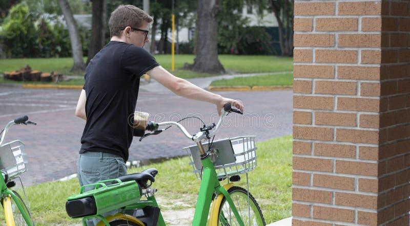 Um homem novo guarda as barras do punho de sua bicicleta foto de stock