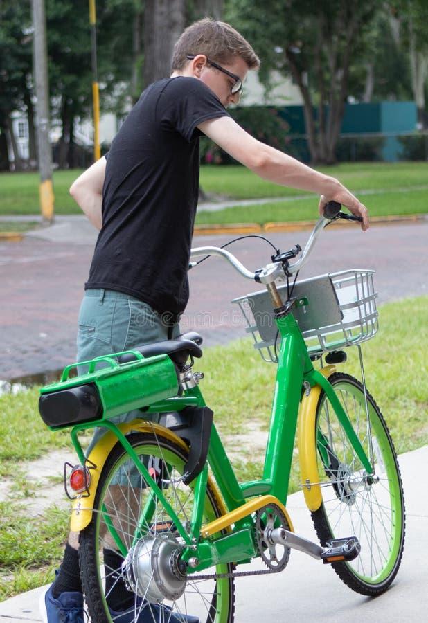 Um homem novo guarda as barras do punho de sua bicicleta foto de stock royalty free