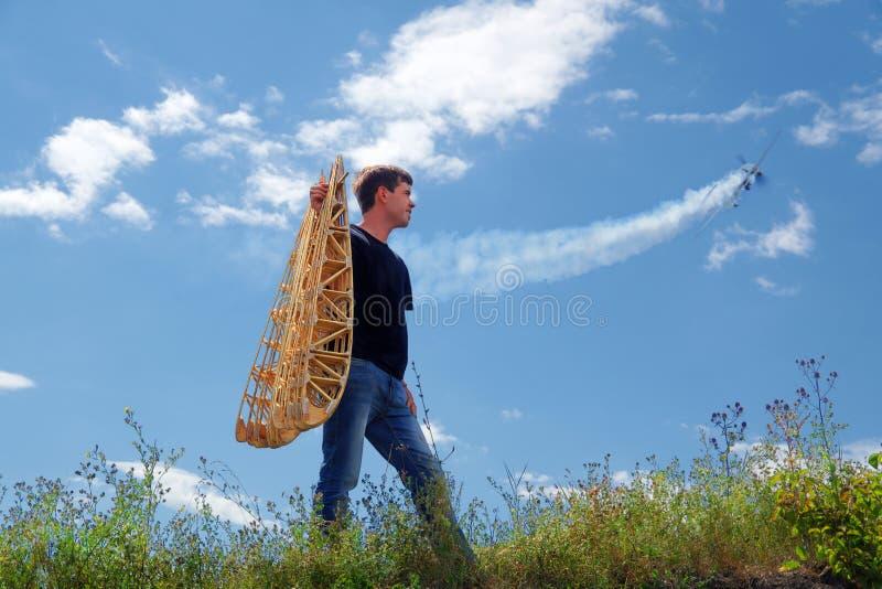 Um homem novo guarda os reforços da asa fotografia de stock