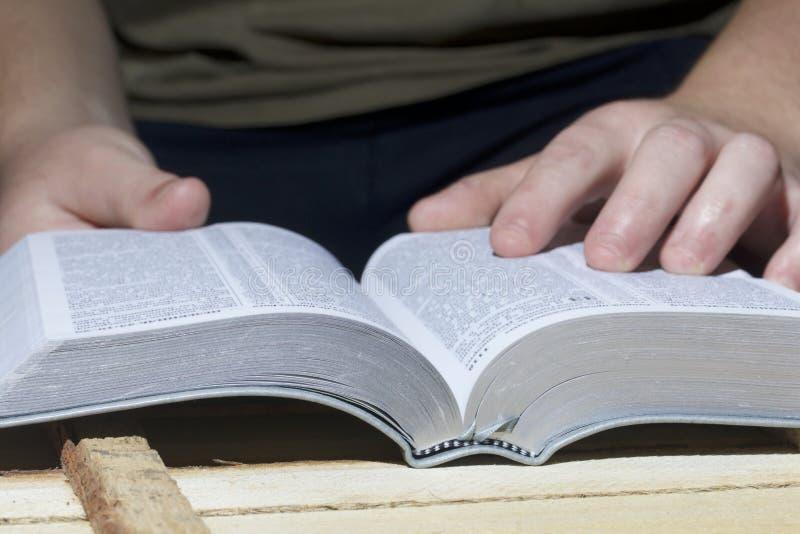 Um homem novo lê a Bíblia, colocando o em uma prancha de madeira das placas fotos de stock royalty free