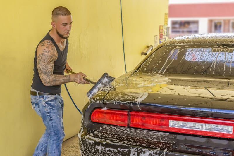 Um homem novo moderno está lavando um carro imagens de stock