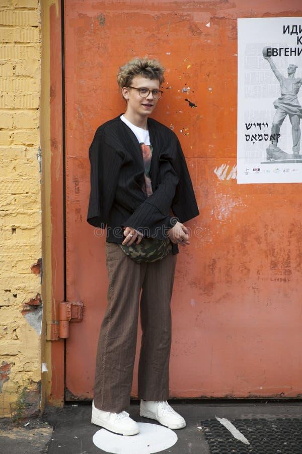 Um homem novo na calças larga bege e em uma camiseta ondulada preta nos vidros está na frente de uma parede de tijolo amarela foto de stock