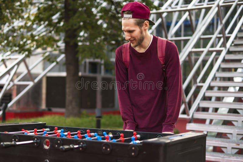 Um homem novo na roupa ocasional que joga o foosball no parque público conceito dos jogos de tabela fotos de stock royalty free