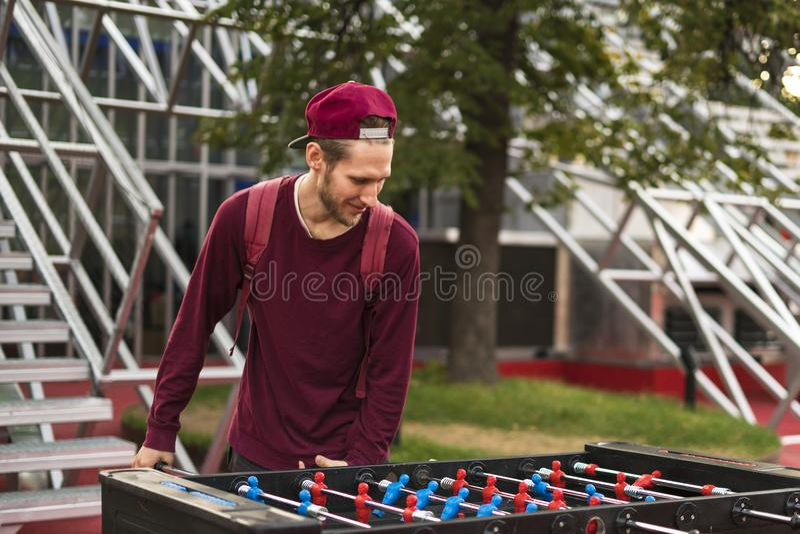 Um homem novo na roupa ocasional que joga o foosball no parque público conceito dos jogos de tabela fotos de stock