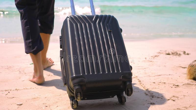 Um homem novo nas calças e em uma camisa clássica com uma mala de viagem anda ao longo da praia contra o contexto do mar de turqu imagens de stock royalty free